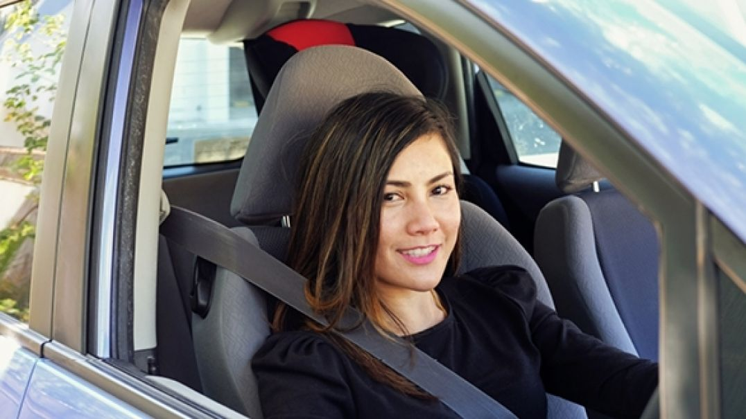 Teenage girl smiling in drivers seat of car
