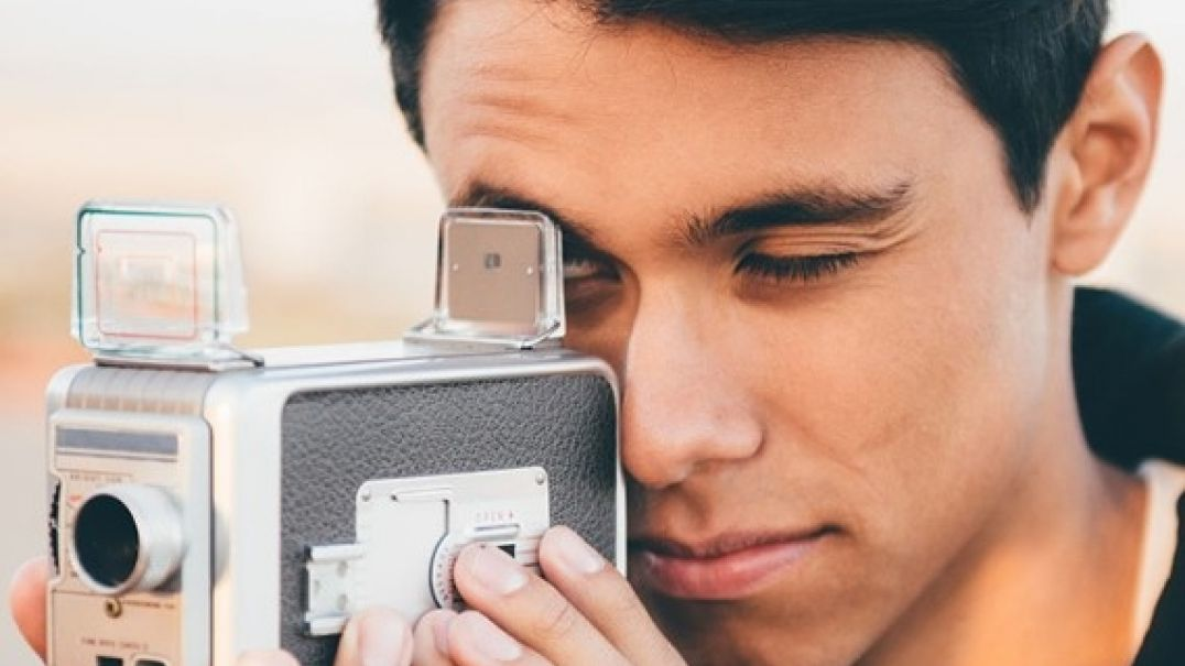 Teenage boy looking into a vintage camera