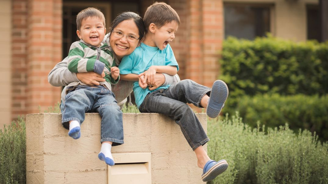 Mum and two kids sitting on a brick letterbox smiling