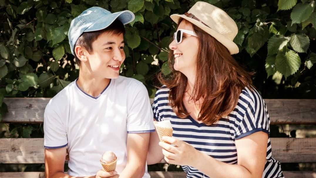 Woman and boy sitting on bench eating ice cream