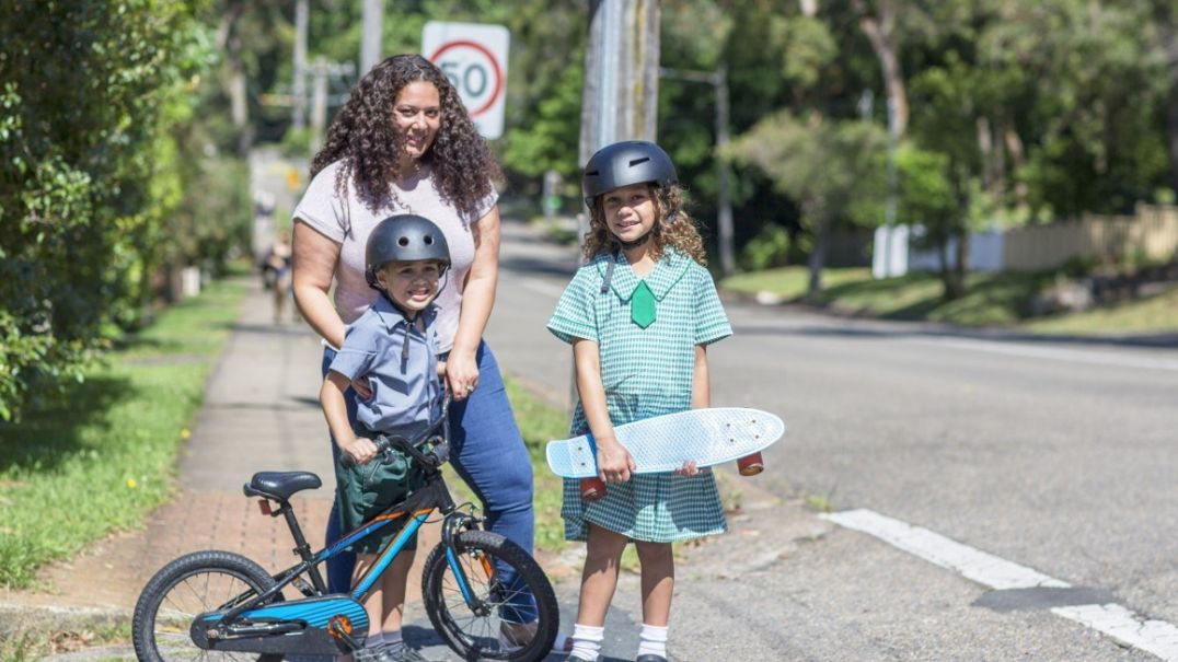 Mum and two children outside holding a bike and skateboard