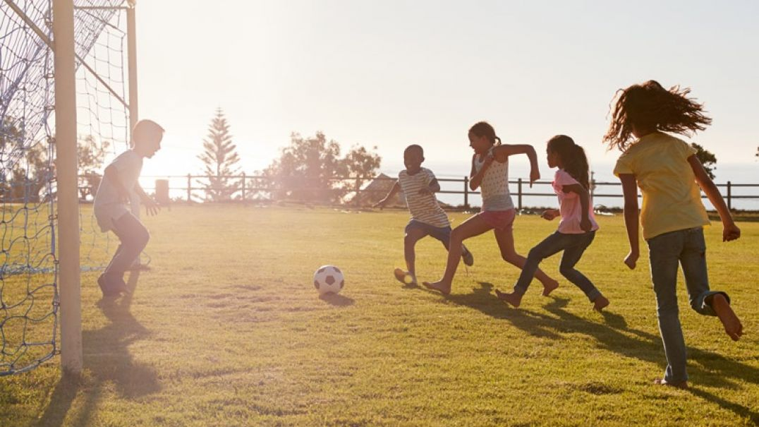 A group of five children outside playing soccer
