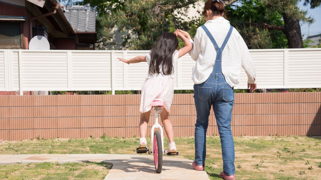 Woman holding child's hand riding a bike