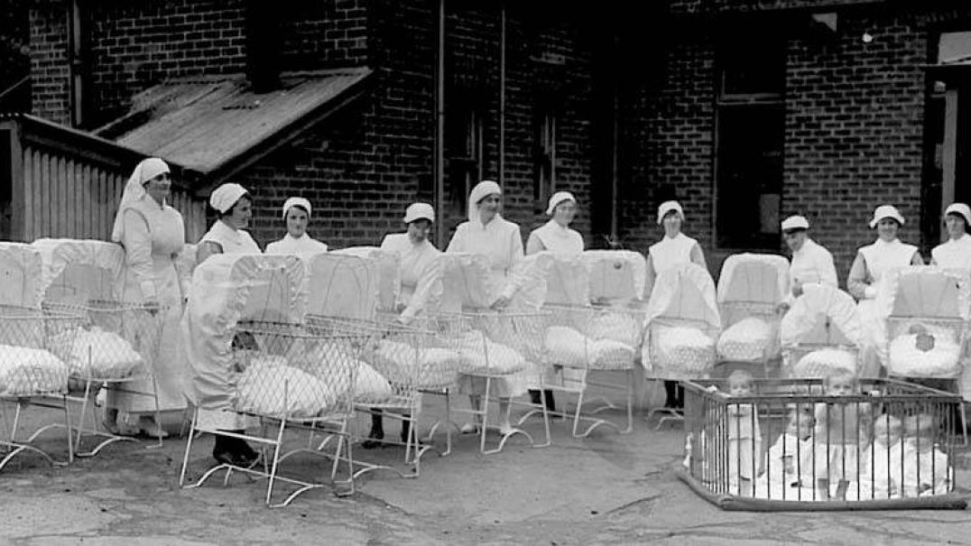 Historical picture of nurses standing outside with babies in cots