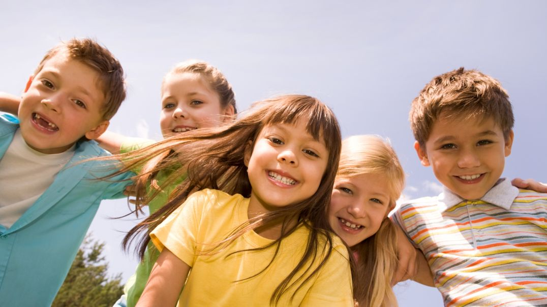 A group of five children smiling