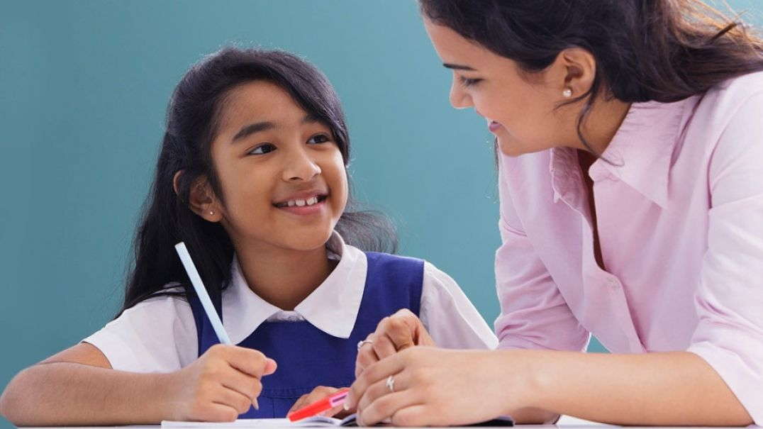 Young girl student smiling at female teacher