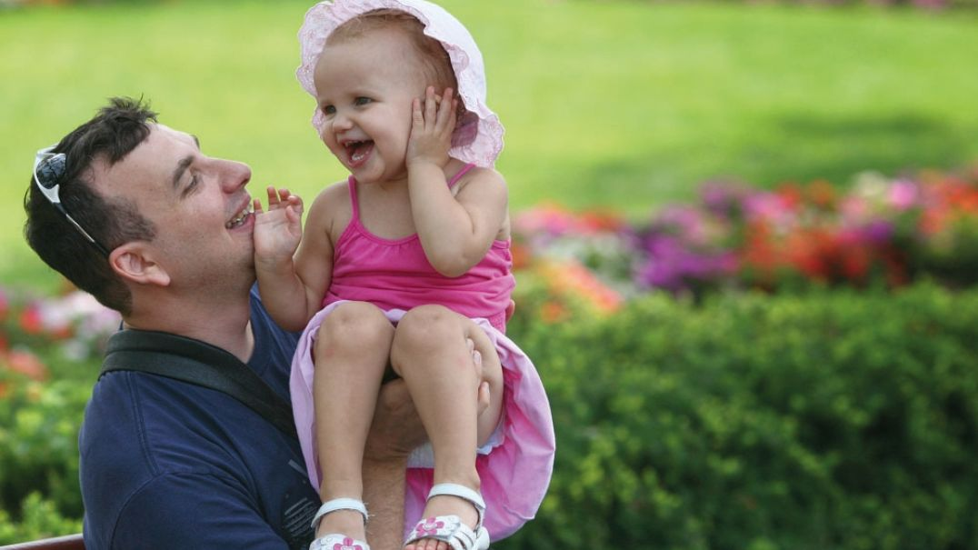 Father holding baby girl at a park bench