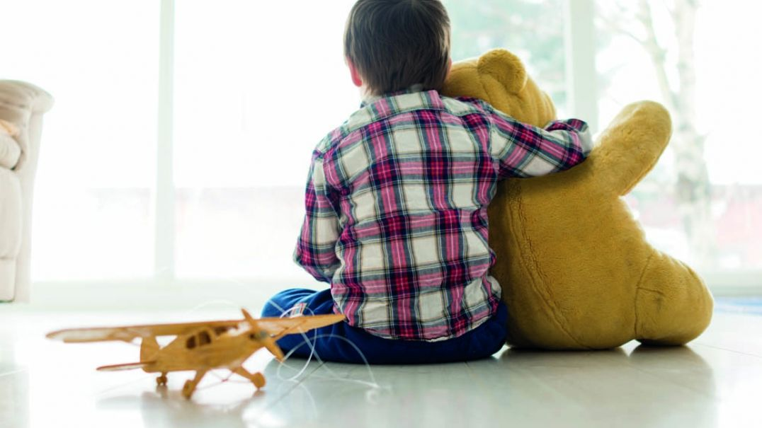 Young boy sitting on floor holding teddy bear