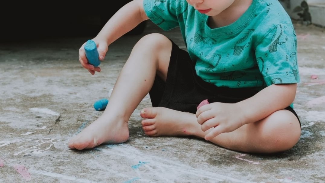 Child in green shirt and black shorts sitting on ground playing with chalk