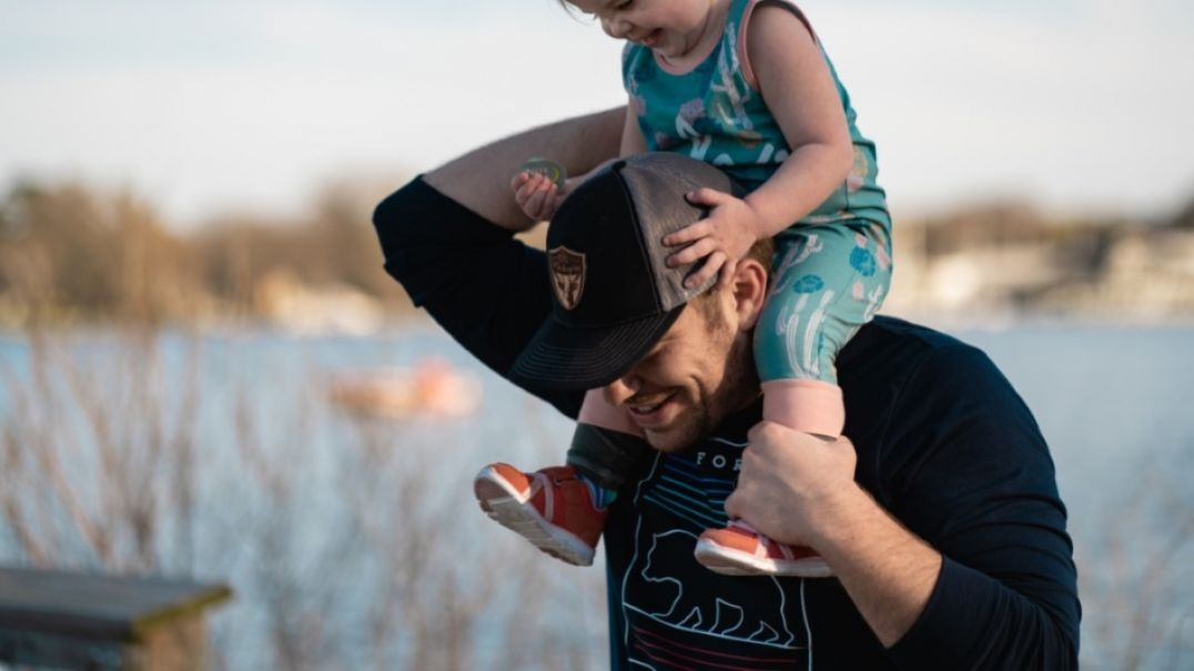 Toddler sitting on mans shoulders