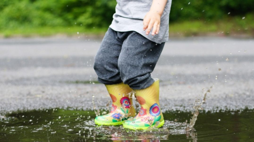 Child wearing gumboots splashing in puddle