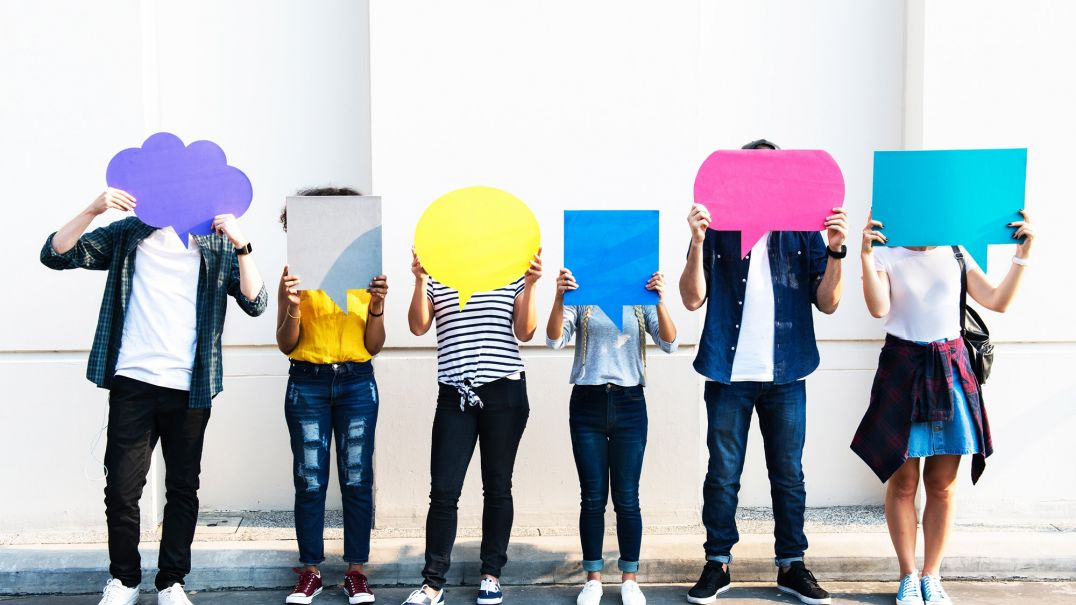 Six people standing holding paper speech bubbles over their faces
