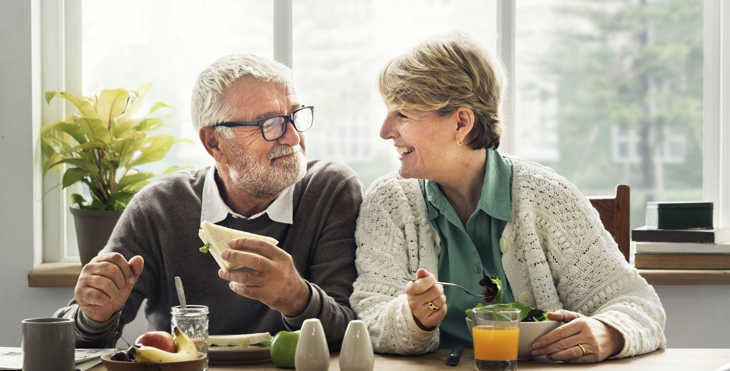 Older couple smiling at each other whilst eating
