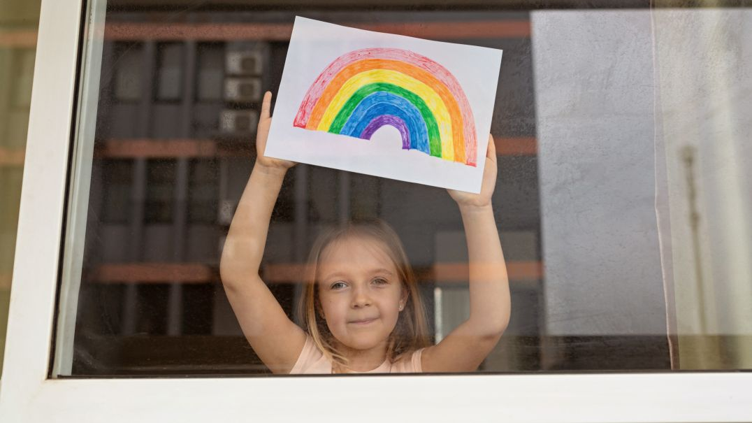 Young girl standing at a window holding up a rainbow drawing
